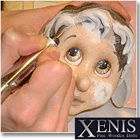 The Artists Of Xenis paint a face by hand